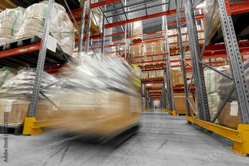 Logistycznie biznes, transport i ładowanie pojęcie - ruch zamazywał obrazek pracownika przewożenia ładowacz z towarami przy magazynem