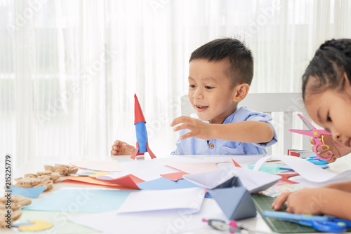 Foto Murales Cute Asian little boy playing with paper rocket while sitting in art class