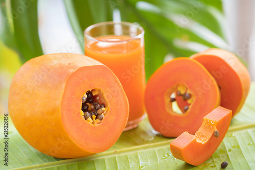 Canvas Sap Tropical exotic papaya fruit and glass jar with smoothie shake juice drink outdoors with palm leaves
