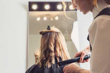 Hairdresser making a hairstyle for client © ansyvan