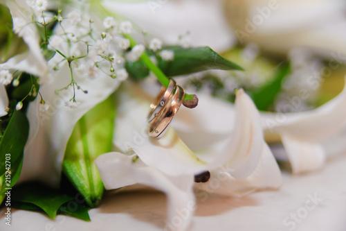 Leinwandbild Motiv lily flower and wedding rings