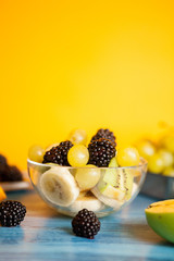 Diet fresh tasty mix of fruits in a bowl on a wooden table. Organic assortment of mixed fruits
