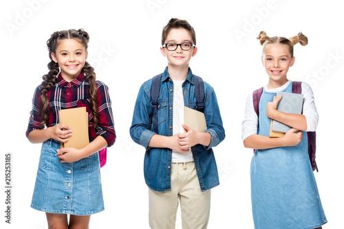 Leinwandbild Motiv three smiling classmates holding books and looking at camera isolated on white