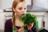 Woman in kitchen holds green aromatic parsley - 215260126
