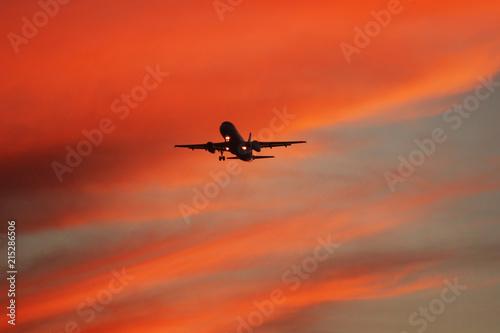 Fototapeta Avión volando en atardecer