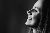 close-up profile face of a beautiful girl who smiling on black and white photo