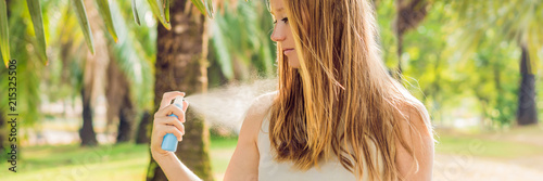 Woman spraying insect repellent on skin outdoor BANNER, long format - 215325506
