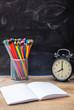 School supplies and alarm clock on wooden desk, blackboard background