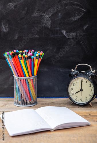 Szkolne dostawy i budzik na drewnianym biurku, blackboard tło