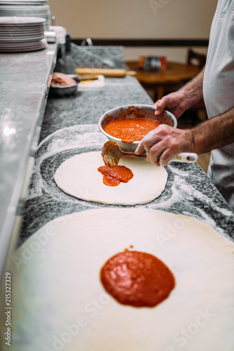Canvas Pizzeria Chef adding tomato sauce. Italian pizza preparation.