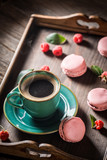 Black coffee and delicious pink macaroons served with hot coffee