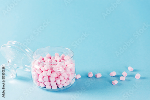 Creative minimal still life on pastel blue colored background. Glass bowl with cute pink marshmallows. Copyspace