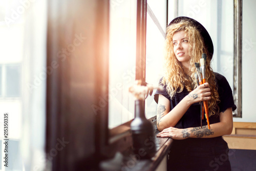 Fototapeta Blonde long hair female artist in black clothes looking in the window, she smiling and holding her brush