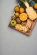 Assorted fresh fruits on plate. Apple, orange, kiwi, pineapple, tangerines on wooden plate. Top view