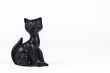 Black cat figurine on white background, copy space