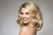 Blonde with curls on a gray background, natural make-up and clean skin. beautiful smile and big eyes. Portrait