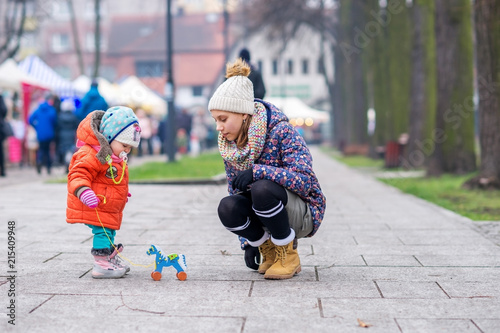 Foto Murales The kid and his older sister play with a wooden horse in cold weather on the street.