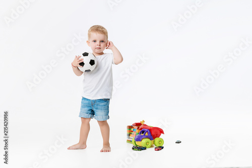 Fotobehang Voetbal Child football player. Kid with a soccer ball in hands on a white isolated background