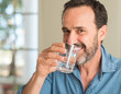 Leinwandbild Motiv Middle age man drinking a glass of water with a happy face standing and smiling with a confident smile showing teeth