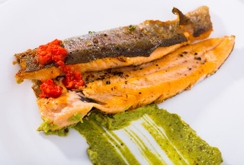 Tasty fried rainbow trout fillet with sauces on plate