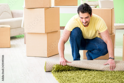 Leinwanddruck Bild Young handsome man moving in to new house with boxes