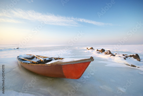 Boat on ice and winter landscape nature composition.