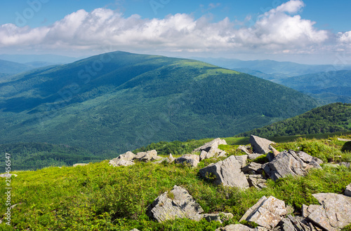rocks among the grass on a hillside. mountain in the distance under the wide cloud formation