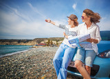 Two young beautiful girls girlfriends traveling together in a car, on the beach on a bright sunny summer day, with map in hand, travel and holidays