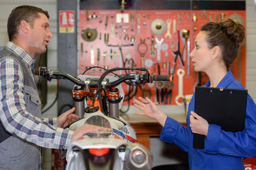 seller and buyer standing in a motorbike workshop