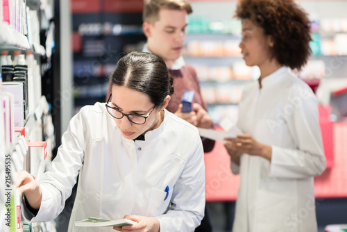 Leinwanddruck Bild Portrait of a female experienced pharmacist reading the indications from the package of a new pharmaceutical product during work in a contemporary drugstore