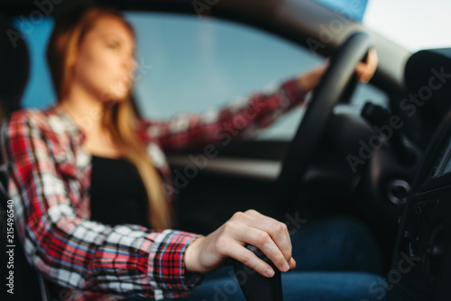 Young woman drives a car - 215496540