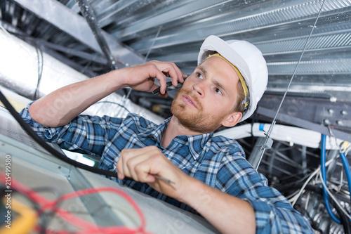 Leinwandbild Motiv young handsome electrician on the phone