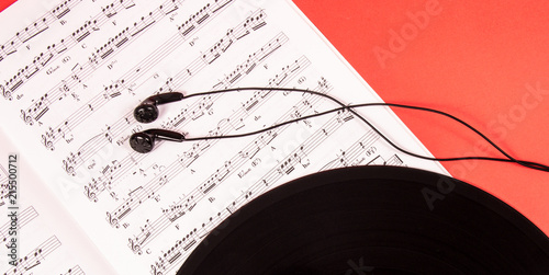 Headphones on music sheets. The concept of creating music. - 215500712