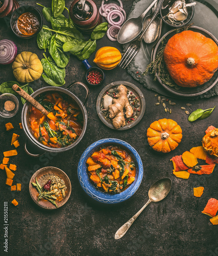 Overhead view of colorful vegetarian pumpkin stew in cooking pot and bowls with spinach and ingredients on dark rustic kitchen table background, top view. Autumn seasonal rustic country food - 215502111