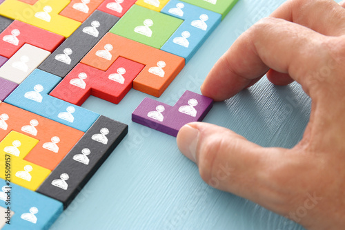 image of tangram puzzle blocks with people icons over wooden table ,human resources and management concept. - 215509157