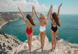 Quadro Free three bestgirlfriends with open arms. Fashion women bikini clothes set. Beautiful traveller girl friends having fun in trendy outfit on cliff mountains enjoying lagoon bay. Summertime vacation.