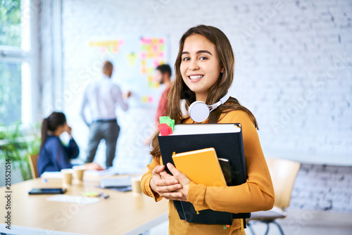 Foto Murales Portrait of female student holding books in classroom. Young woman looking at camera and smiling