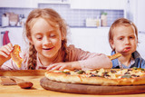 We love pizza!  Cute little girls best friends eating pizza. Humorous photo.