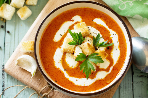 Puree soup tomato with croutons and cream in a bowl close-up on a kitchen wooden table. Diet menu. The concept of healthy eating. - 215528363