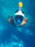 El niño esta buceando en la piscina con easybreath snorkeling mask