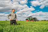 Unternehmerisches Handeln - Junger Landwirt betrachtet stolz seinen Getreidebestand - 215549771