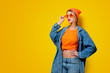Young style girl in jeans clothes with orange glasses on yellow background. Clothes in 1980s style