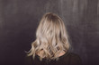 Woman With Mid Length Blonde Wavy Shadow Root Hairstyle
