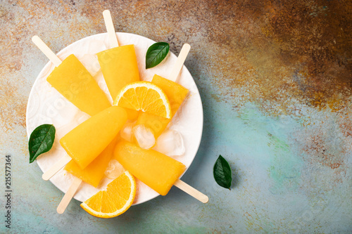 Canvas Sap Orange popsicles with juice on a rusty blue bacground. Ice pops, flat lay, top view with copy space