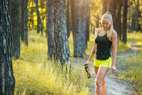 Foto Spatwand Hardlopen Beautiful blonde athletic woman on a run in the forest