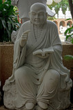 Statue of Chinese priest carved from white marble.