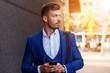 Leinwandbild Motiv Businessman looking at his mobile phone while walking on street to office.