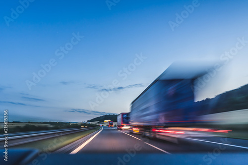 obraz lub plakat Background photograph of a highway. Truck on a motorway, motion blur, light trails. Evening or night shot of trucks doing logistics and transportation on a highway.