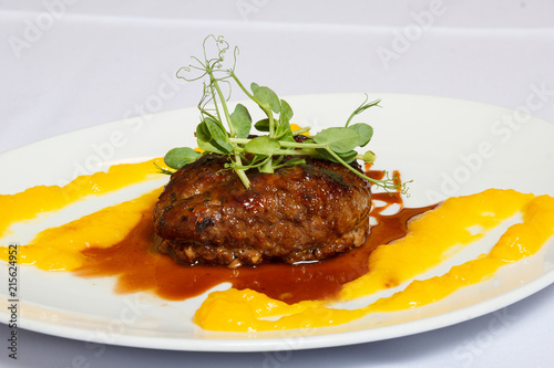 Chop with greenery and sauce on a white dish - 215624952