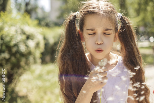 Cute little 10 years old girl in casual outfit playing at park in warm summer day. She blows on dandelion flower. Copy space - 215630777